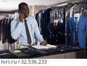 Купить «Smiling afro-american man tailor taking order at counter in sewing workshop», фото № 32536233, снято 6 апреля 2020 г. (c) Яков Филимонов / Фотобанк Лори