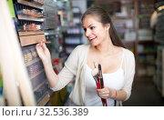Купить «Positive woman customer shopping various pencils», фото № 32536389, снято 15 декабря 2019 г. (c) Яков Филимонов / Фотобанк Лори