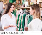 Купить «Two young women friends talking in clothes shop and smiling», фото № 32536425, снято 15 марта 2018 г. (c) Яков Филимонов / Фотобанк Лори