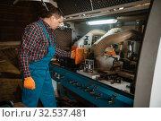 Carpenter in uniform near woodworking machine. Стоковое фото, фотограф Tryapitsyn Sergiy / Фотобанк Лори