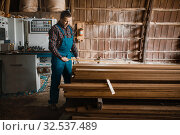 Carpenter with measuring tape measures boards. Стоковое фото, фотограф Tryapitsyn Sergiy / Фотобанк Лори