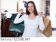 Купить «Cute girl customer with packs delighted from purchases», фото № 32538341, снято 17 января 2018 г. (c) Яков Филимонов / Фотобанк Лори