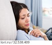 Купить «Sad young woman thinking on sofa in home interior», фото № 32538409, снято 18 апреля 2018 г. (c) Яков Филимонов / Фотобанк Лори
