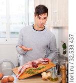 Man holding lamb carcass in domestic kitchen. Стоковое фото, фотограф Яков Филимонов / Фотобанк Лори