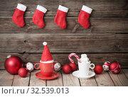 Купить «Christmas red and white decor on old wooden background», фото № 32539013, снято 18 ноября 2019 г. (c) Майя Крученкова / Фотобанк Лори