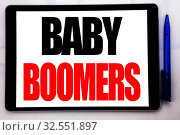 Conceptual hand writing text caption inspiration showing Baby Boomers. Business concept for Demographic Generation written on tablet computer on the white background in the office. Стоковое фото, фотограф Zoonar.com/Artur Szczybylo / easy Fotostock / Фотобанк Лори