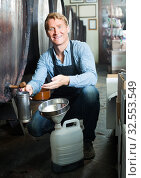 Купить «man pouring wine from wood in cellar», фото № 32553549, снято 6 июня 2020 г. (c) Яков Филимонов / Фотобанк Лори