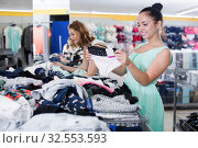 Купить «Young happy woman selecting new basics pants», фото № 32553593, снято 19 июня 2017 г. (c) Яков Филимонов / Фотобанк Лори