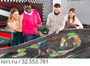 Girls with guys play slot car racing models. Стоковое фото, фотограф Яков Филимонов / Фотобанк Лори