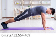 Купить «Young man exercising at home in sports and healthy lifestyle con», фото № 32554409, снято 3 мая 2017 г. (c) Elnur / Фотобанк Лори