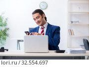 Купить «Young male businessman sitting in the office», фото № 32554697, снято 20 июня 2019 г. (c) Elnur / Фотобанк Лори