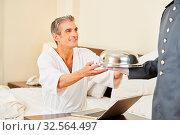 Page als Zimmerservice bringt einem Mann mit Laptop im Hotel das Essen. Стоковое фото, фотограф Zoonar.com/Robert Kneschke / age Fotostock / Фотобанк Лори
