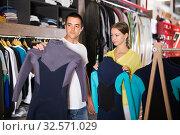 Купить «Couple searching wetsuits for surf», фото № 32571029, снято 7 октября 2019 г. (c) Яков Филимонов / Фотобанк Лори
