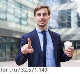 Купить «Man in jacket walking with coffee and pointing finger», фото № 32571149, снято 29 апреля 2017 г. (c) Яков Филимонов / Фотобанк Лори
