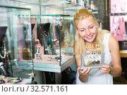 Купить «Young smiling woman shopping earrings», фото № 32571161, снято 6 августа 2020 г. (c) Яков Филимонов / Фотобанк Лори