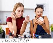 Купить «Two smiling young women friends doing make-up at table with cosmetics», фото № 32571197, снято 29 августа 2018 г. (c) Яков Филимонов / Фотобанк Лори