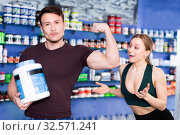 Купить «Athletic guy showing muscles while standing in store of sports nutritional supplements», фото № 32571241, снято 12 апреля 2018 г. (c) Яков Филимонов / Фотобанк Лори
