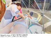 Russia, Samara, July 2017: A female doctor massage a woman lying down with a mechanical roller in the massage room on the embankment of the Volga River . Редакционное фото, фотограф Акиньшин Владимир / Фотобанк Лори