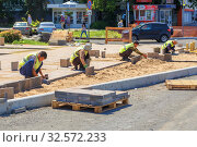 Купить «Russia, Samara, July 2017: working guest workers laying paving slabs in the city on the streets of the Young Guard in Sunny Summer Day.», фото № 32572233, снято 7 июля 2017 г. (c) Акиньшин Владимир / Фотобанк Лори