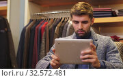Man working on tablet PC at clothing store. Стоковое видео, видеограф Илья Шаматура / Фотобанк Лори