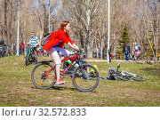 Russia, Samara, April 2017: sports girl cycling for the opening of the bike season in the city park on a spring sunny day. Редакционное фото, фотограф Акиньшин Владимир / Фотобанк Лори