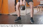 Купить «Sports training indoors - an athletic man squatting with a weight in his hands», видеоролик № 32573137, снято 29 мая 2020 г. (c) Константин Шишкин / Фотобанк Лори