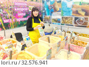 Russia, Samara, April 2017: a young saleswoman selling Siberian honey at the city fair. The text in Russian: clover, kiprei, linden, honey, and other names of honey. Редакционное фото, фотограф Акиньшин Владимир / Фотобанк Лори