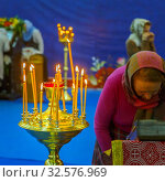 Купить «Russia, Samara, April 2017: a believing woman performs the worship of the ark with a part of the relics of St. Seraphim of Sarov. Burning candles in standing in a candlestick. Text in Russian: samara.», фото № 32576969, снято 21 апреля 2017 г. (c) Акиньшин Владимир / Фотобанк Лори