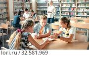 Купить «Teenage students working in groups in college library», видеоролик № 32581969, снято 27 мая 2020 г. (c) Яков Филимонов / Фотобанк Лори