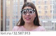 Купить «Ophthalmology treatment - a young smiling woman sitting in the optometry device for vision test», видеоролик № 32587913, снято 24 февраля 2020 г. (c) Константин Шишкин / Фотобанк Лори