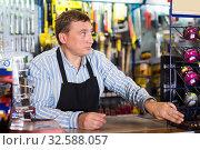 Купить «Attentive seller man in store is trading tools», фото № 32588057, снято 22 октября 2019 г. (c) Яков Филимонов / Фотобанк Лори