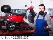 Positive man worker demonstrating motorbikes. Стоковое фото, фотограф Яков Филимонов / Фотобанк Лори