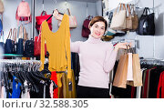 Купить «Glad young woman enjoying her purchases», фото № 32588305, снято 7 февраля 2017 г. (c) Яков Филимонов / Фотобанк Лори