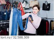 Купить «Customer checks the quality of jeans», фото № 32588309, снято 7 февраля 2017 г. (c) Яков Филимонов / Фотобанк Лори