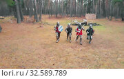 Купить «Four men knightes running in the row in the forest in full metal armour holding swords - day time», видеоролик № 32589789, снято 30 мая 2020 г. (c) Константин Шишкин / Фотобанк Лори