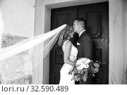 The kiss. Groom kisses bride on forehead in front of church portal. Стоковое фото, фотограф Matej Kastelic / Фотобанк Лори