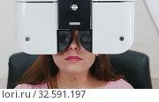 Купить «Ophthalmology treatment - a young woman with bright pink lips checking her visual acuity with a special optometry equipment», видеоролик № 32591197, снято 24 февраля 2020 г. (c) Константин Шишкин / Фотобанк Лори