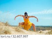 Купить «Girls in yellow dress and Gasmask dancing on the sand dunes», фото № 32607997, снято 25 апреля 2019 г. (c) Aleksejs Bergmanis / Фотобанк Лори