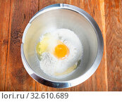 Купить «Cooking of pie - top view of pile of flour with broken egg in steel bowl», фото № 32610689, снято 29 января 2020 г. (c) easy Fotostock / Фотобанк Лори