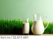 Glass of milk and jar on fresh grass meadow background. Стоковое фото, фотограф Zoonar.com/Ivan Mikhaylov / easy Fotostock / Фотобанк Лори