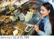 Купить «Cheerful beautiful girl choosing delicious ganaches», фото № 32615789, снято 31 марта 2020 г. (c) Яков Филимонов / Фотобанк Лори
