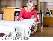 Купить «aged female customer looking for beautiful fabric in textile shop», фото № 32615829, снято 15 февраля 2017 г. (c) Яков Филимонов / Фотобанк Лори