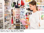 Купить «Interested young woman choosing colorful ribbons and braid for d», фото № 32615985, снято 18 октября 2019 г. (c) Яков Филимонов / Фотобанк Лори