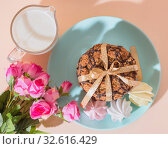 Fresh baked oatmeal crispy cookies on a blue plate on a background of peach color, milk, French multi-colored meringues. Delicious culinary sweet dessert, romantic festive breakfast, food, snacks. Стоковое фото, фотограф Светлана Евграфова / Фотобанк Лори