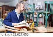 Купить «Portrait of positive professional man carpenter standing with book in furniture repair shop», фото № 32627653, снято 19 ноября 2018 г. (c) Яков Филимонов / Фотобанк Лори