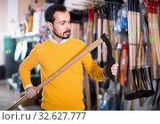Купить «Man choosing various tools in garden equipment shop», фото № 32627777, снято 2 марта 2017 г. (c) Яков Филимонов / Фотобанк Лори