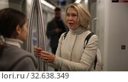 Купить «Portrait of mature woman talking friendly with her fellow traveler in modern subway car», видеоролик № 32638349, снято 11 ноября 2019 г. (c) Яков Филимонов / Фотобанк Лори