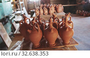 Купить «Various handmade utensils from baked clay on floor and on racks in pottery workshop», видеоролик № 32638353, снято 28 мая 2020 г. (c) Яков Филимонов / Фотобанк Лори