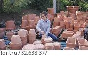 Купить «Female customer is standing near clay pots in stock», видеоролик № 32638377, снято 8 ноября 2019 г. (c) Яков Филимонов / Фотобанк Лори