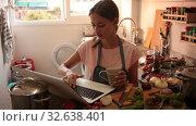 Купить «Cheerful young female using her laptop at kitchen», видеоролик № 32638401, снято 28 августа 2019 г. (c) Яков Филимонов / Фотобанк Лори